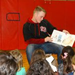 Student reads book to students in the gym