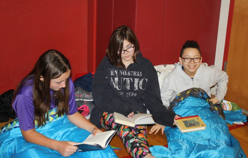 Students get comfortable as they prepare to begin reading their books