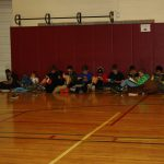 Students lined up against the mats as they read books